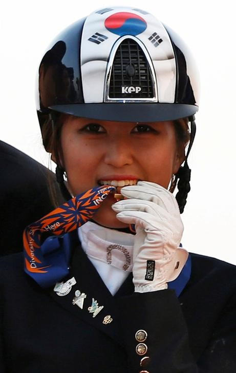 South Korea's Chung Yoo-ra, then known as Chung Yoo-yeon, bites her gold medal after winning the equestrian dressage team competition at the 17th Asian Games in Incheon. Photo: Reuters/Kim Hong-ji