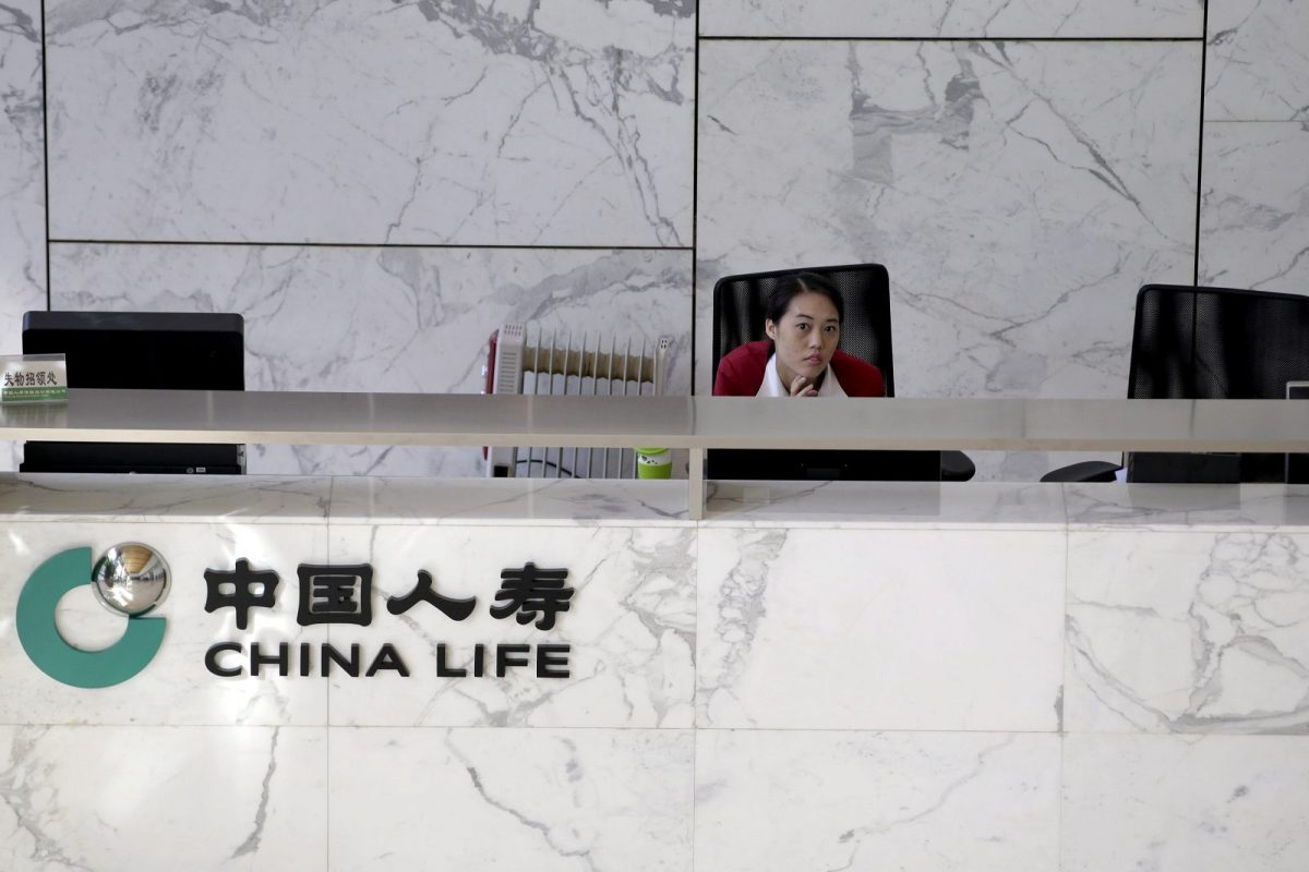 An employee sits at the reception of the headquarters building of China Life insurance in Beijing, China, March 24, 2016. Photo: Reuters/Jason Lee
