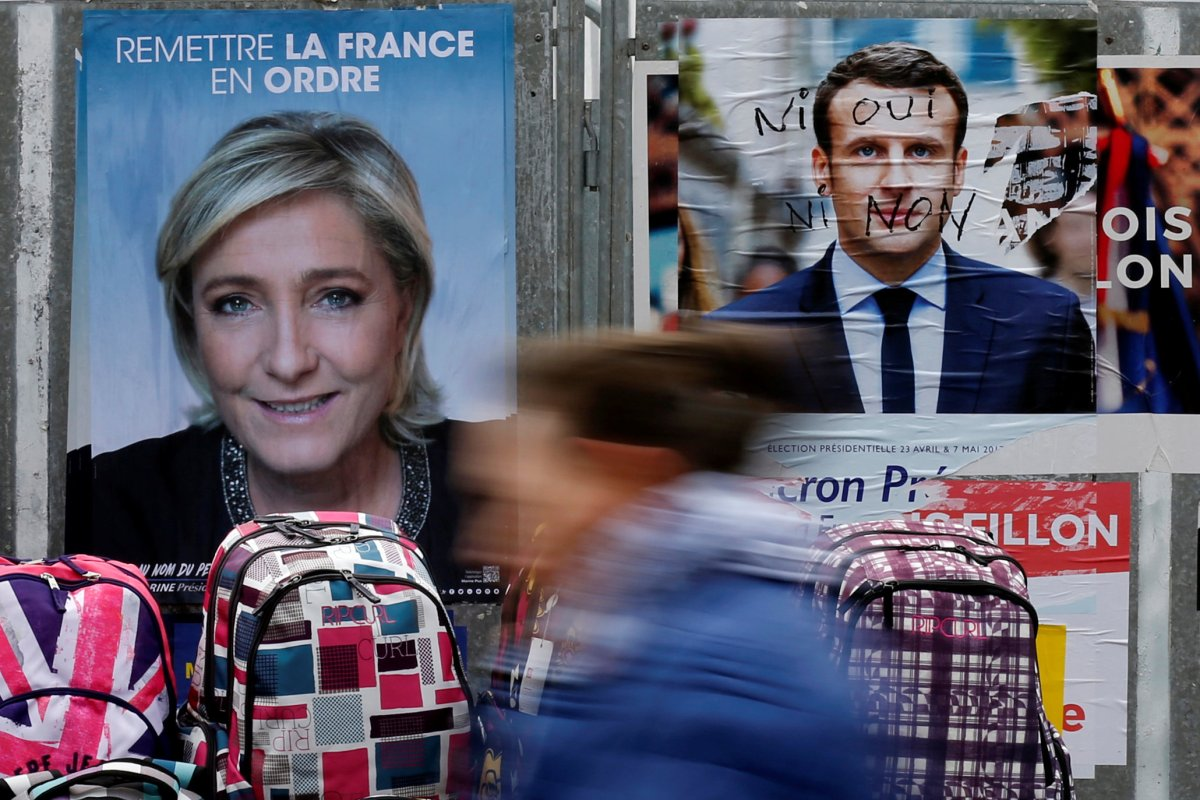 A woman walks past campaign posters for Marine Le Pen (L) and Emmanuel Macro. Photo: Reuters/Pascal Rossignol