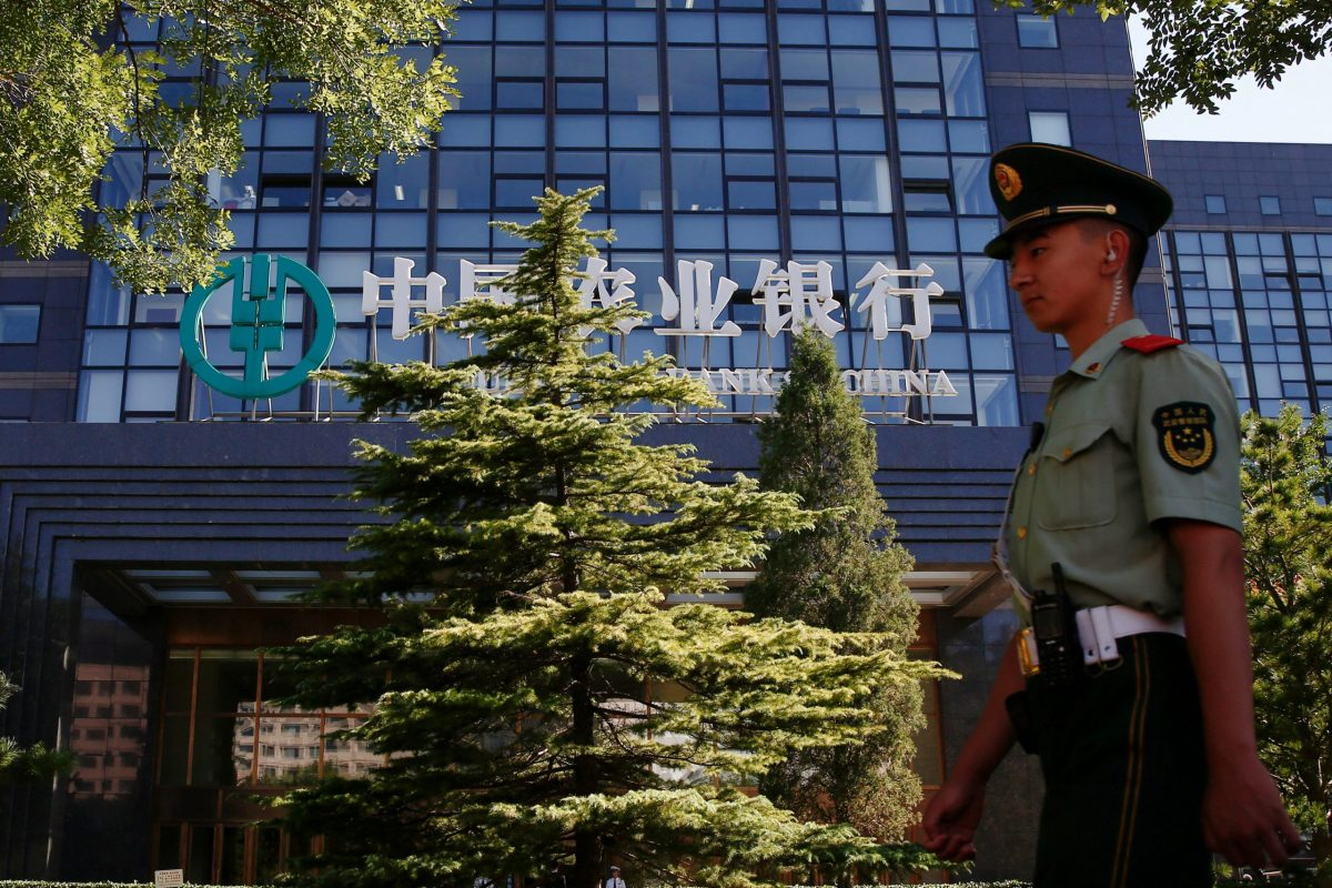 A paramilitary policeman walks past an Agricultural Bank of China building in Beijing, China. Photo: Reuters, Thomas Peter