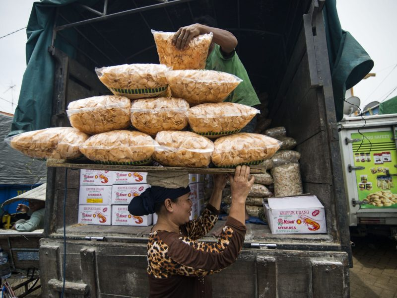 An Indonesian woman carrying bags of foodstuff at a market in Surabaya. Photo: AFP