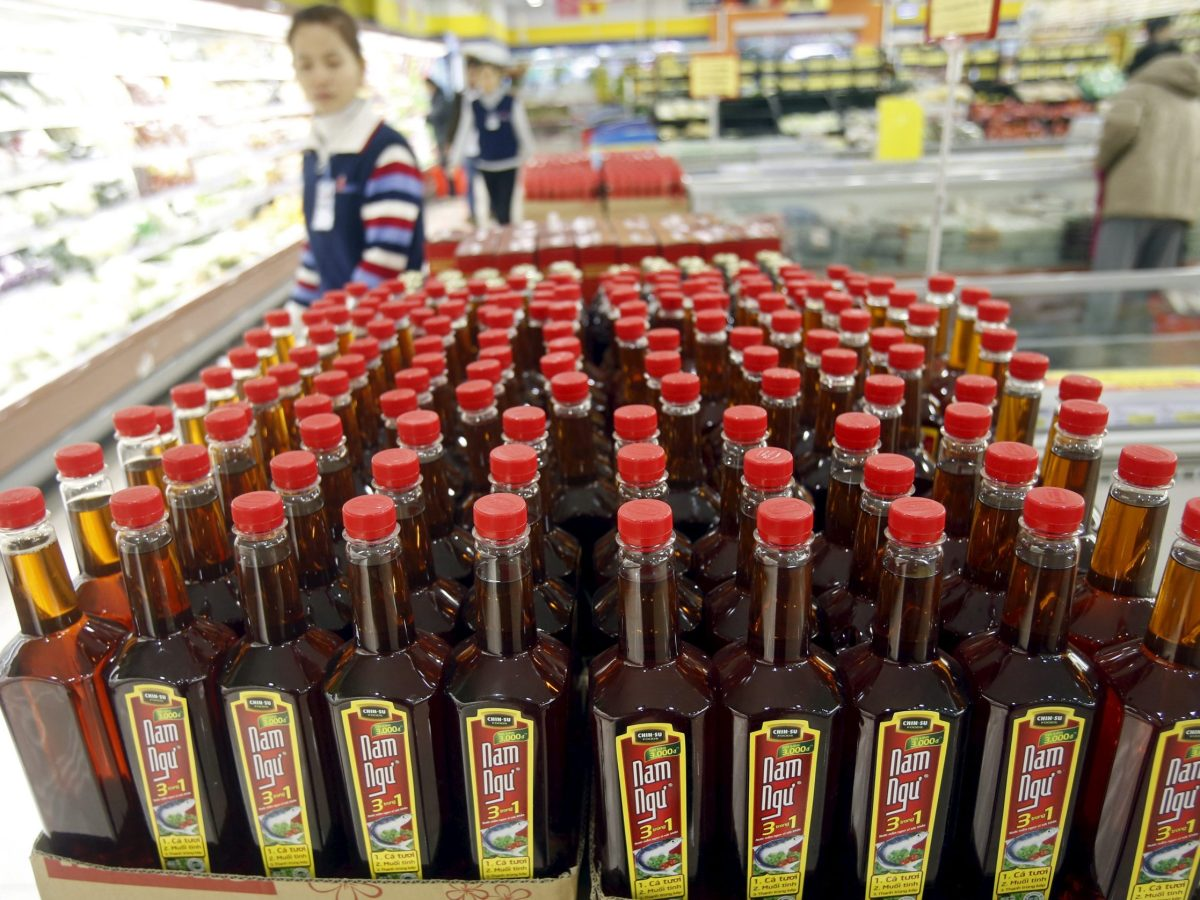 A woman walks near bottles of Nam Ngu fish sauce, produced by Masan Group, at a supermarket in Hano. Photo: Retuers