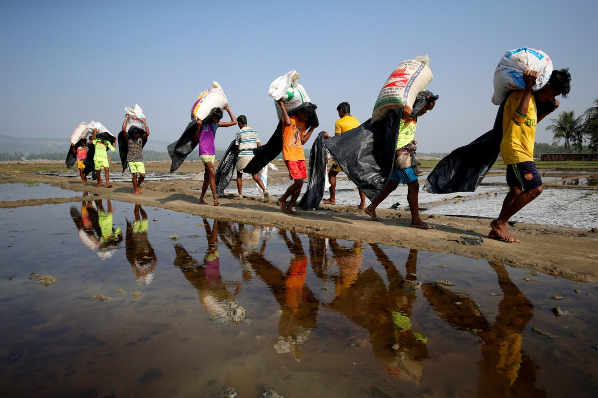 Rohingya refugee workers carry bags of salt as they work in processing yard in Cox's Bazar, Bangladesh. Photo: Reuters/Mohammad Ponir Hossain