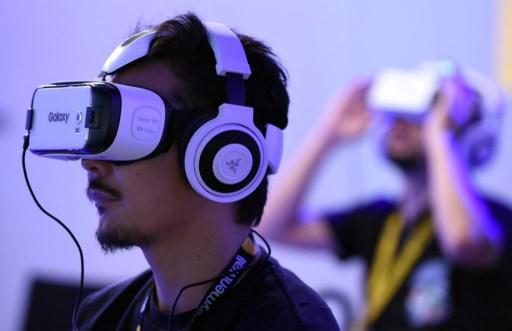 "People play with virtual reality head gear ""Gear VR"" of Oculus. Photo: AFP, Toru Yamanaka"