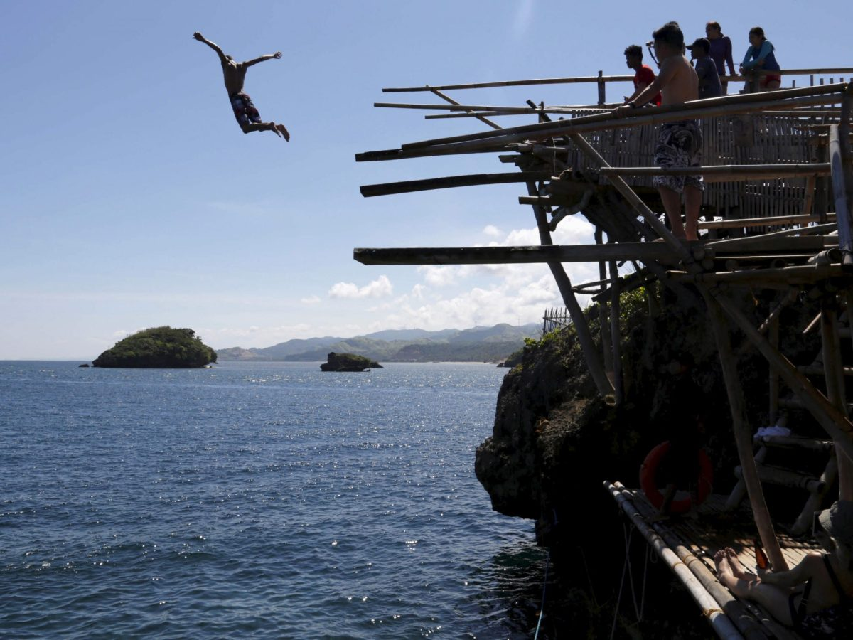 A tourist jumps off a 20-foot cliff at one of the islets off the island of Boracay, central Philippines January 18, 2016.  Photo: Reuters /Charlie Saceda