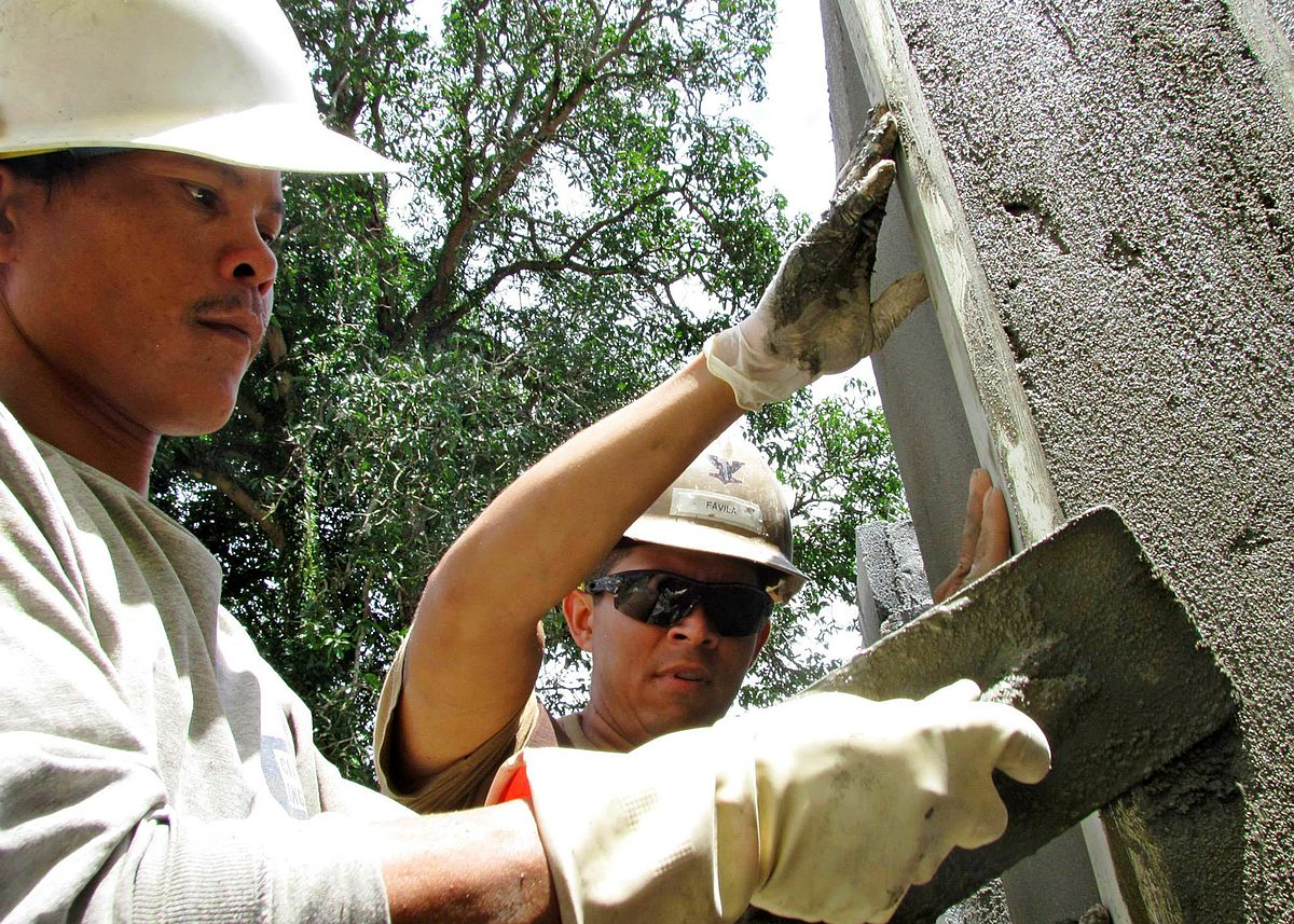 U.S. Navy Builder 3rd Class Zavier Favila, center, and a Cambodian worker apply stucco to the walls of a school in Cambodia. Photo: U.S. Navy/Released