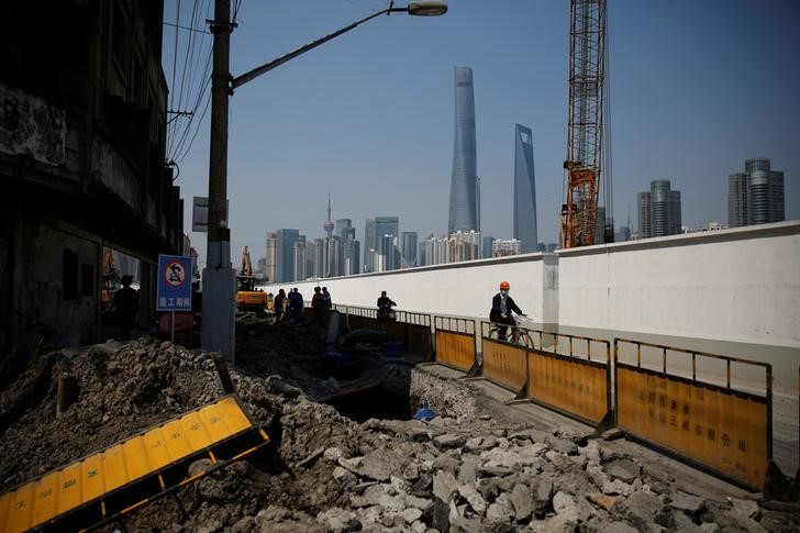 Workers at a construction site in front of Shanghai's financial district of Pudong. Photo: Reuters/Aly Song