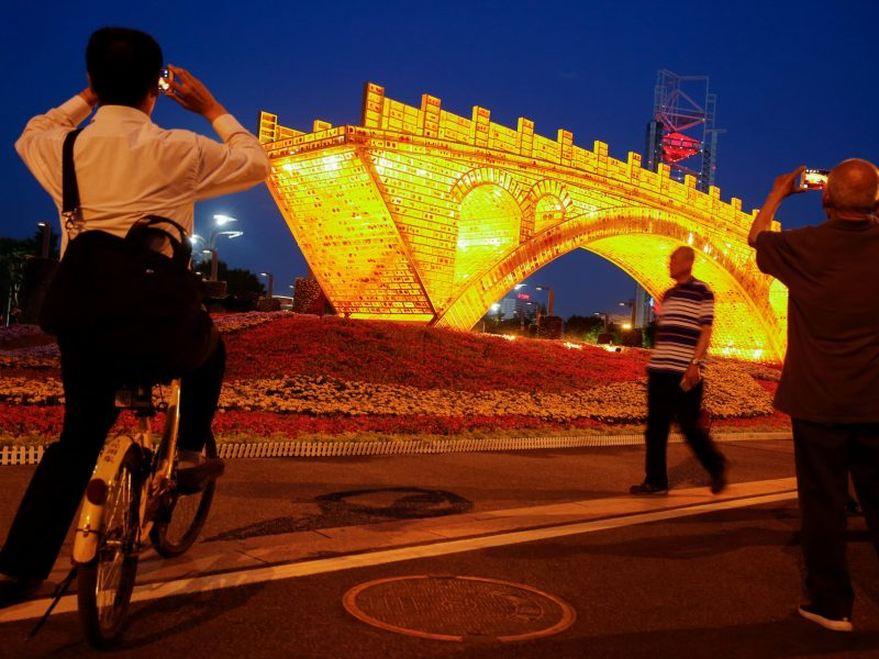 "People take pictures of the ""Golden Bridge on Silk Road"" installation by Chinese artist Shu Yong, set up ahead of May's Belt and Road Forum in Beijing. Photo: Reuters, Thomas Peter"