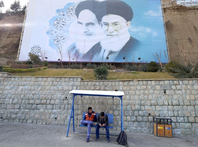 Iranian youths sit under a large picture of Iran's late leader Ayatollah Ruhollah Khomeini (left), and Iran's Supreme Leader Ayatollah Ali Khamenei at a park in Tehran, Iran, January 17, 2016. Photo: Reuters / Raheb Homavandi