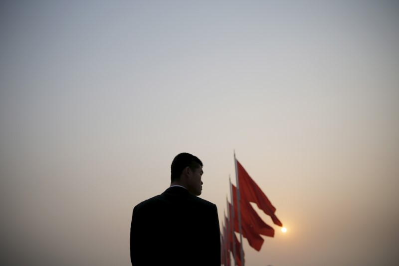 A security agent stands guard near the Great Hall of the People in Beijing's Tiananmen Square as the sun appears through the smog. Photo: Reuters/Damir Sagolj