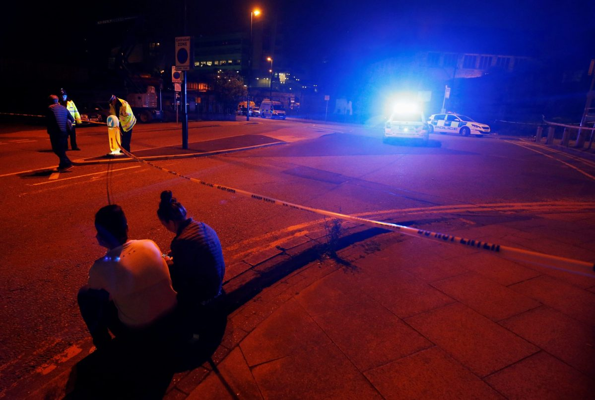People sit by the side of the road next to a police cordon outside the Manchester Arena,  where Ariana Grande had been performing, in Manchester, northern England. Photo: Reuters