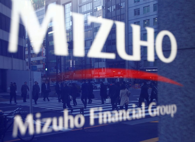 Pedestrians are reflected on Mizuho Bank's signboard in Tokyo. Photo: Reuters/Kim Kyung-hoon