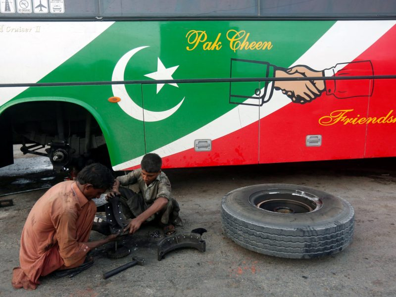 Workers repair the brakes on a bus on a road in Karachi, Pakistan. Photo: Reuters.