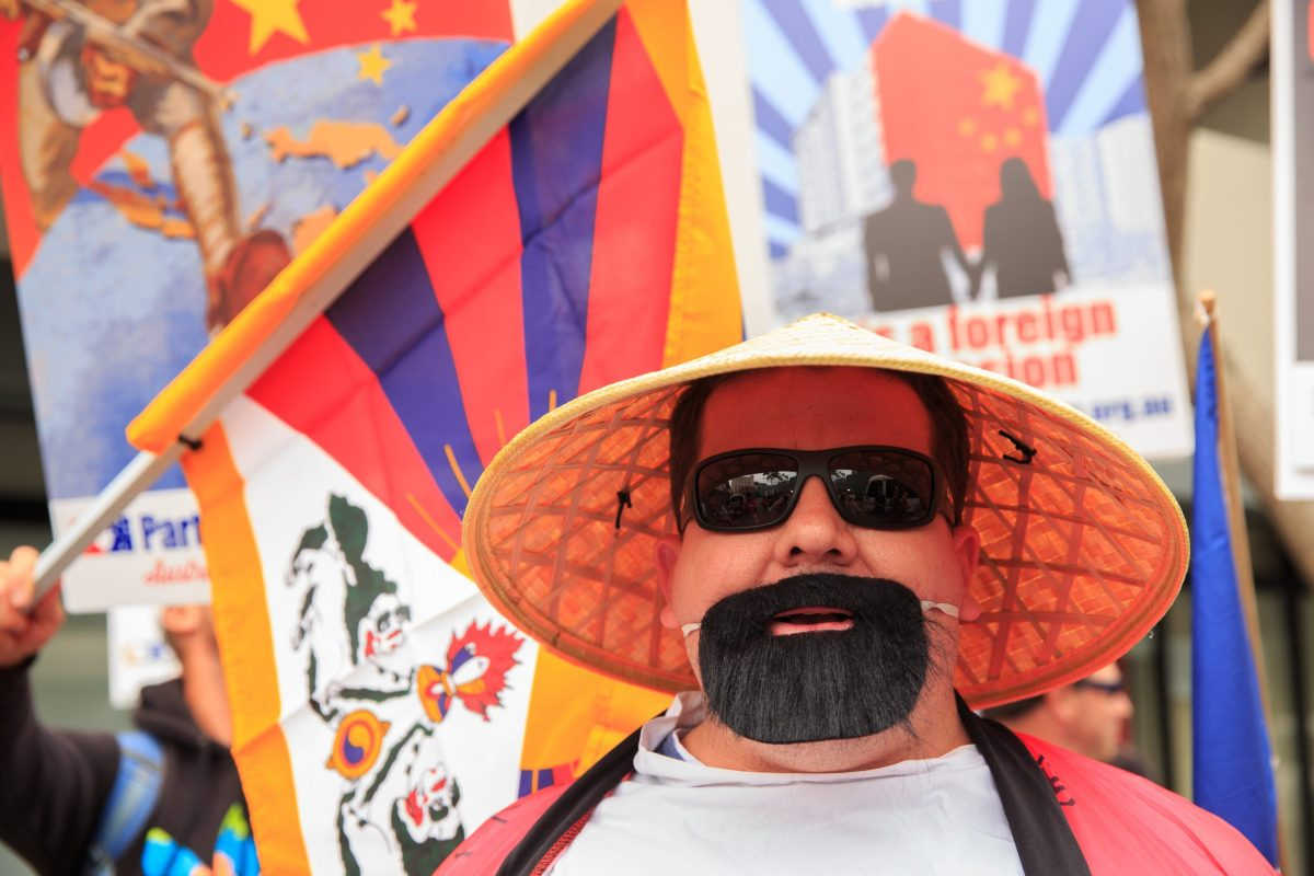 A protester from a right-wing minor political group, the Party of Freedom, wears an Asian conical hat and fake beard at a demonstration outside the Chinese Consulate in Camperdown, Sydney. Protesters demonstrated against an alleged Chinese 'Real Estate Invasion of Australia' as well as 'Cultural Genocide' due to an increased number of Chinese-born new Australians. Photo: AFP Forum/Richard Ashen