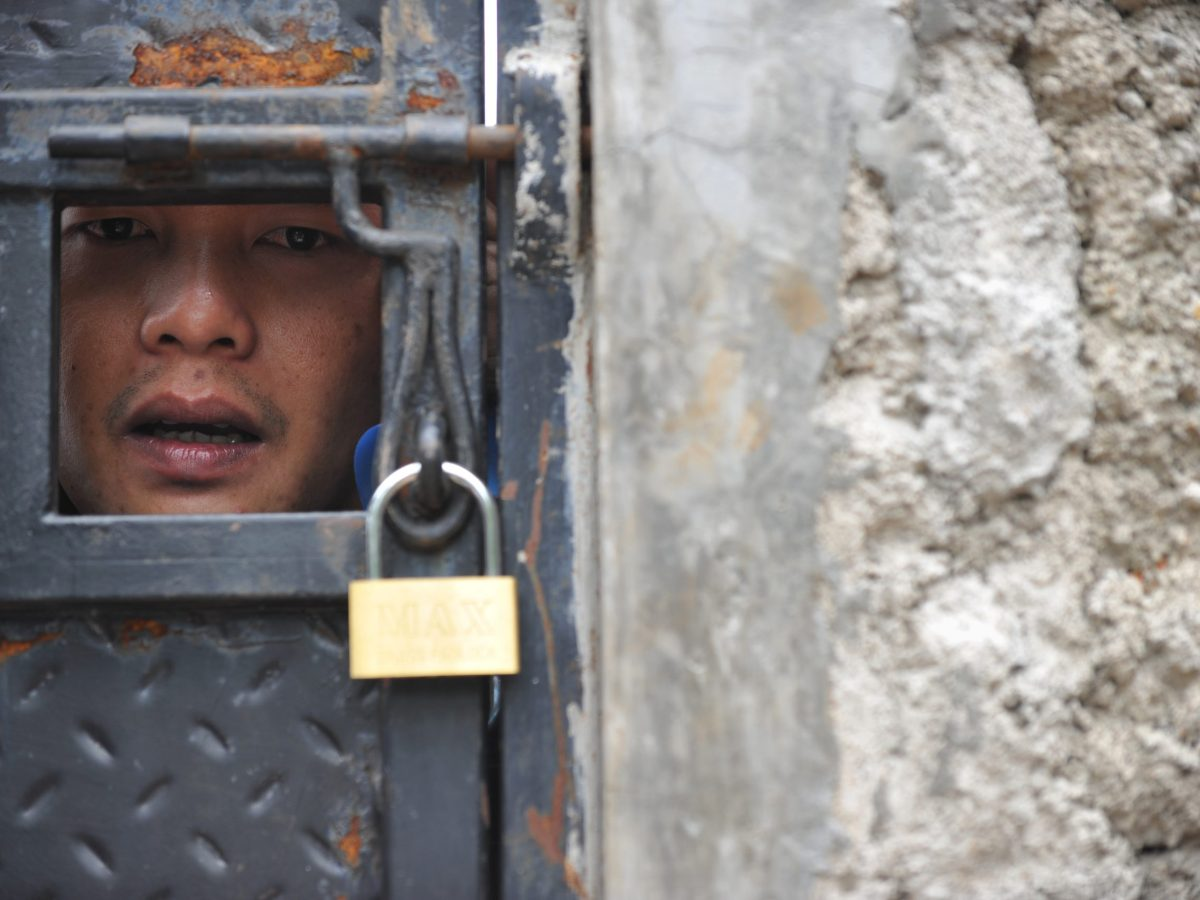 TO GO WITH AFP STORY INDONESIA-RELIGION-RIGHTS-ISLAM-AHMADIYAH, FOCUS BY ARLINA ARSHAD This picture taken on April 9, 2013 shows cleric of the Ahmadiyah Islamic sect, Rahmat Rahmadijaya, speaking through a door during an AFP interview at Al Misbah mosque in Bekasi.  A group of minority Ahmadiyah Muslims in Indonesia have been holed up in a mosque since authorities shuttered it earlier this month, in a stand-off that starkly illustrates the growing religious intolerance sweeping the country.   AFP PHOTO / ADEK BERRY / AFP PHOTO / ADEK BERRY