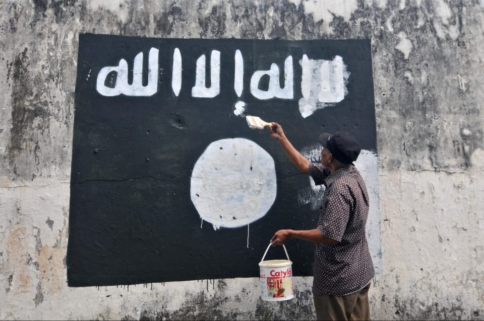 A government worker removes ISIS (Islamic State of Iraq and Syria) flags painted on to walls near Veteran Street in Surakarta City, Indonesia, in an attempt to discourage the promotion of the jihadist group in the region. Photo: AFP Forum/Agoes Rudianto