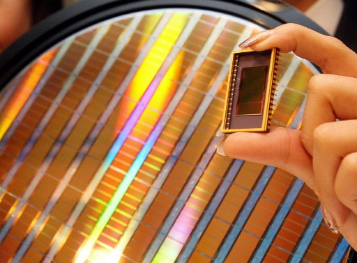 An employee of Samsung Electronics shows the world's first 30-nanometer 64-gigabit NAND flash memory device. Photo: AFP/Kim Jae-hwan