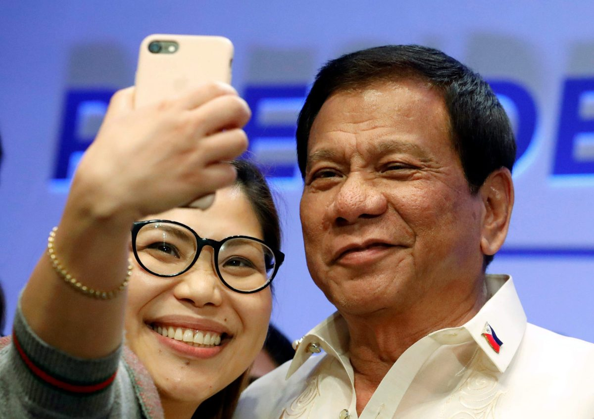 A journalist takes a selfie with Philippine President Rodrigo Duterte after a news conference in Manila, Philippines April 29, 2017.  REUTERS/Erik De Castro - RTS14GCC