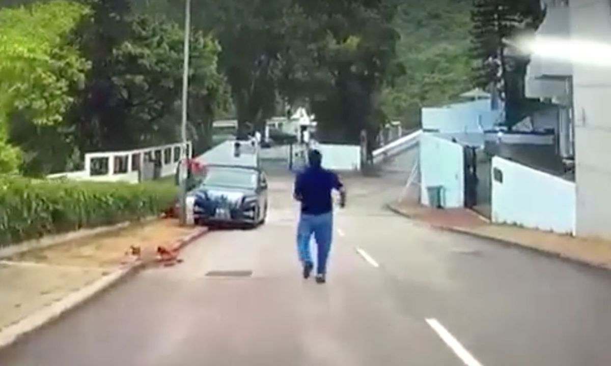 A man is chasing his car, which is sliding backwards down a slope. Photo: Kelvin Leug