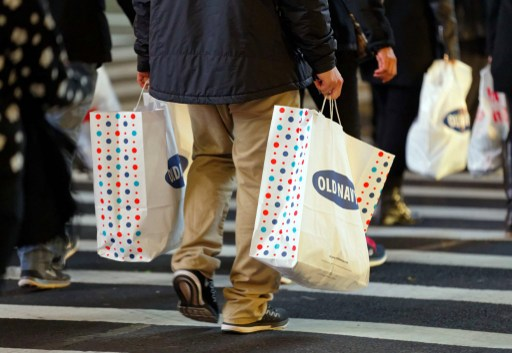 A man carries shopping bags as he crosses the street in New York. Photo: AFP