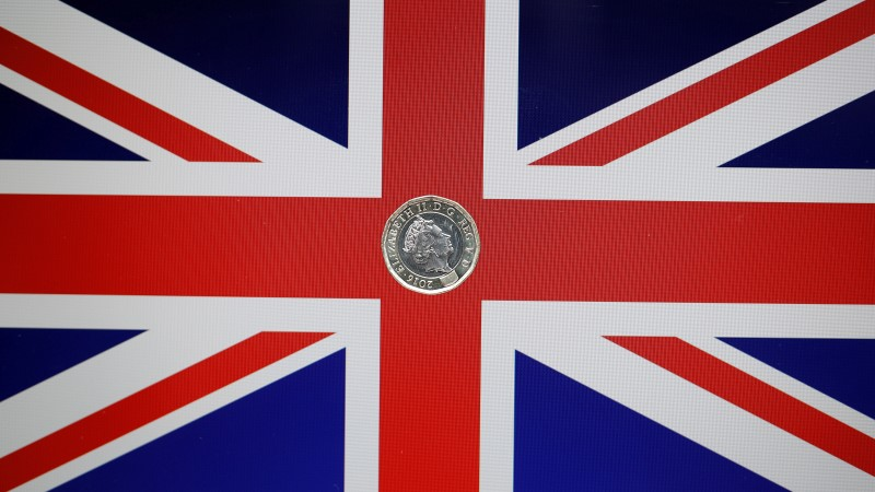 A one pound coin lies on a Union Flag in a photo illustration shot May 3, 2017. Reuters/Darren Staples