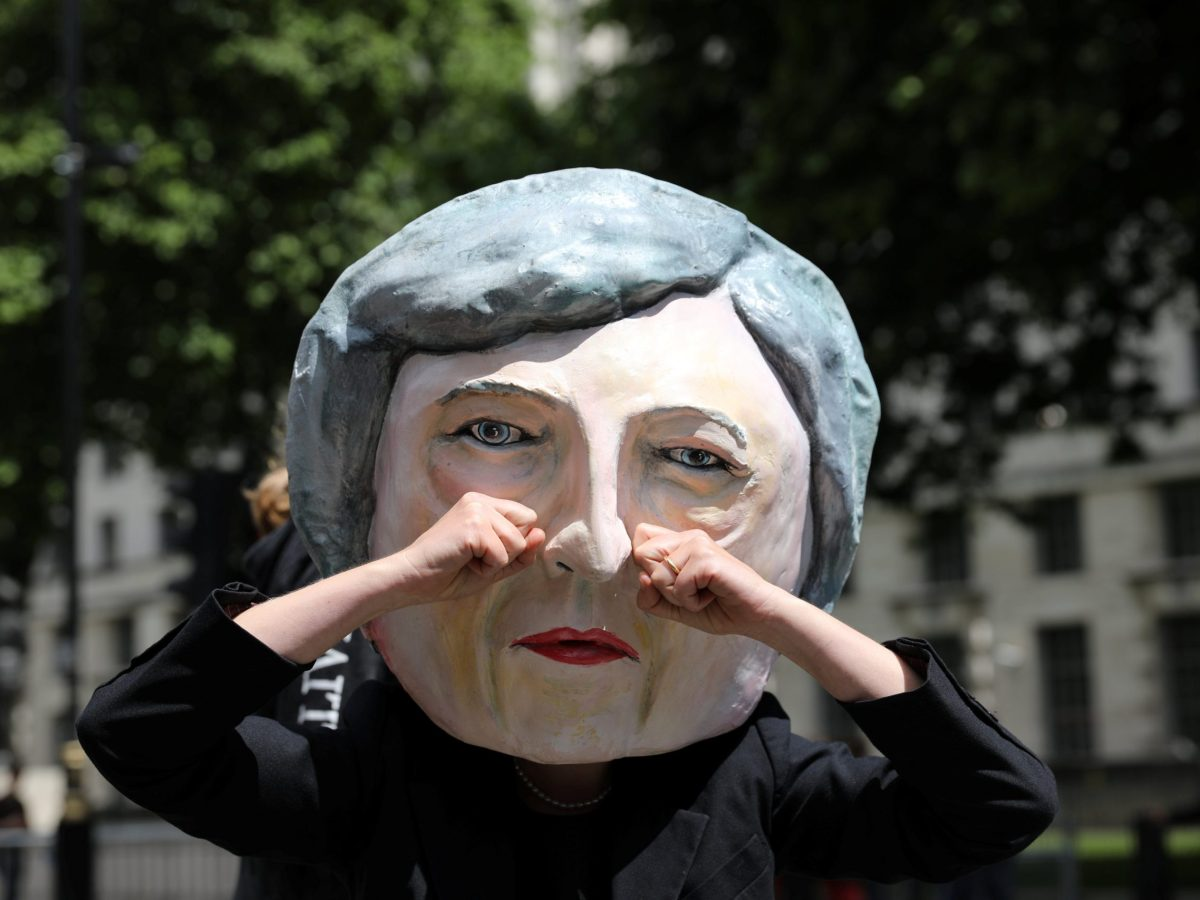 A protester wears a Theresa May mask. Photo: Reuters/Marko Djurica