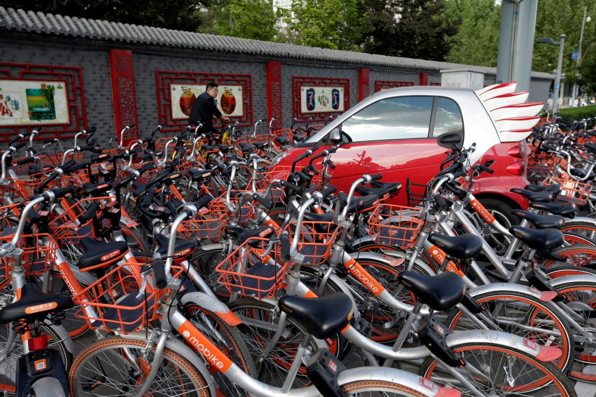 Mobike's shared bikes are parked around a car in Beijing, China April 21, 2017. Photo: Reuters/Jason Lee