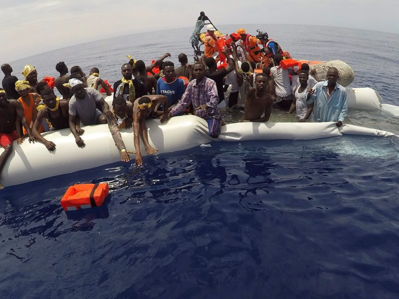 "Migrants on a sinking dinghy wait to be rescued by ""Save the Children"" NGO crew from the ship Vos Hestia in the mediterranean . Photo: Reuters/Stefano Rellandini"