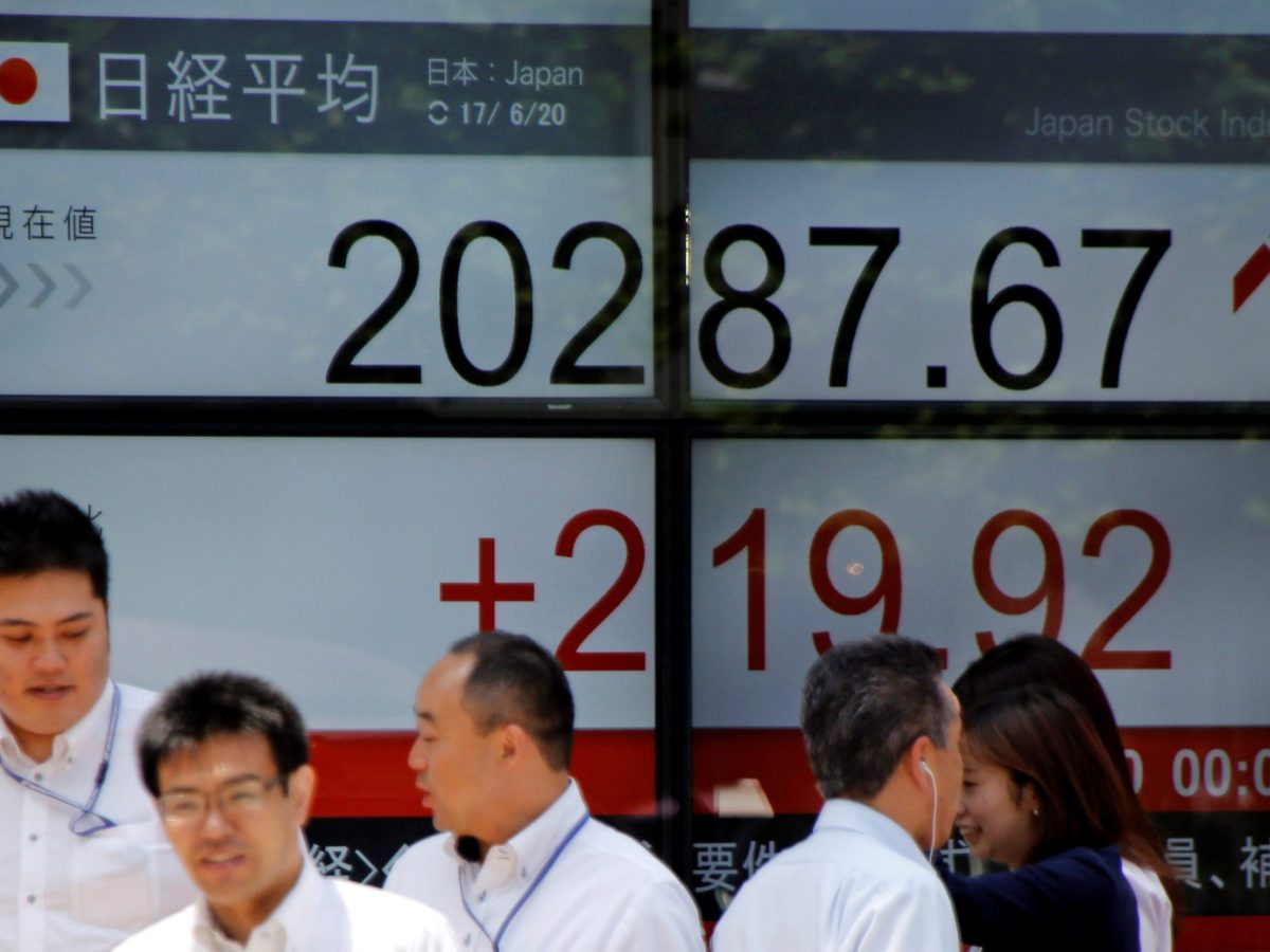 People walk past an electronic board showing Japan's Nikkei average outside (red for gains) a brokerage in Tokyo. Photo: Reuters / Toru Hanai