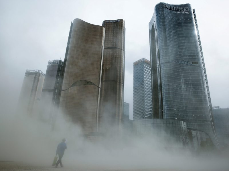A man walks through a cloud of dust whipped up by wind at the construction site near newly erected office skyscrapers in Beijing. Photo: Reuters/Thomas Peter