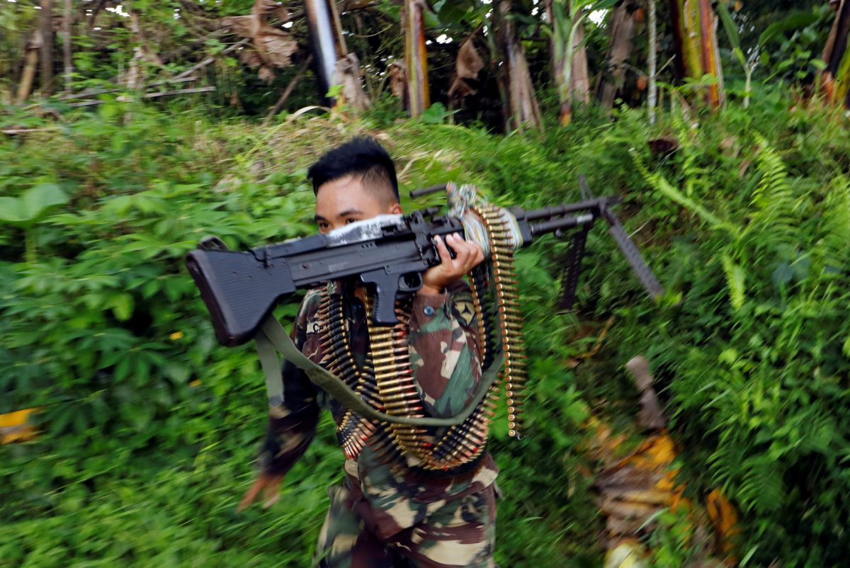 A Philippines army soldier runs with a machine gun in Marawi city. Photo: Reuters/Jorge Silva