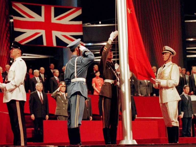China's flag is raised by People's Liberation Army soldiers to signal Hong Kong's return to Chinese sovereignty after 156 years of British rule, in Hong Kong, July 1, 1997. Photo: Reuters / Dylan Martinez