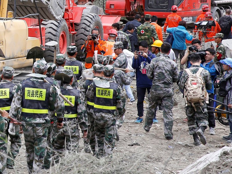 Members of the media take pictures of rescue workers at the site of a landslide in the village of Xinmo, Mao county, Sichuan province. Photo: Reuters/Aly Song