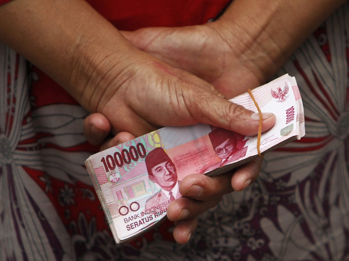 A woman holds behind her back a stack of Indonesian rupiah banknotes. Photo: Reuters/Beawiharta