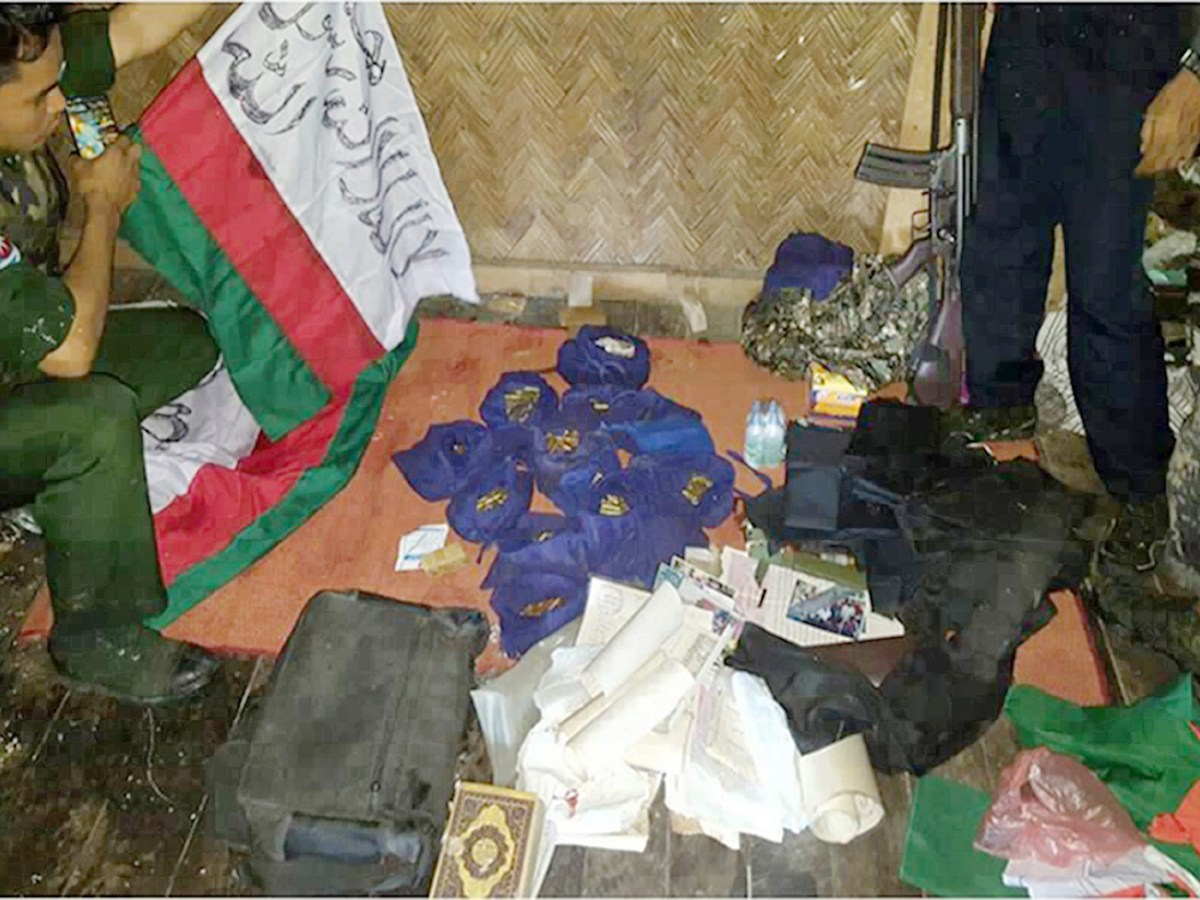 A photograph released by Myanmar's Armed Forces on October 14, 2016 with a Myanmar soldier holding a banner with Arabic writing with pouches containing bullets and documents seized inside a house during military operations in search of attackers in Maungdaw located in Rakhine State. Photo: AFP/Myanmar Armed Forces/Stringer