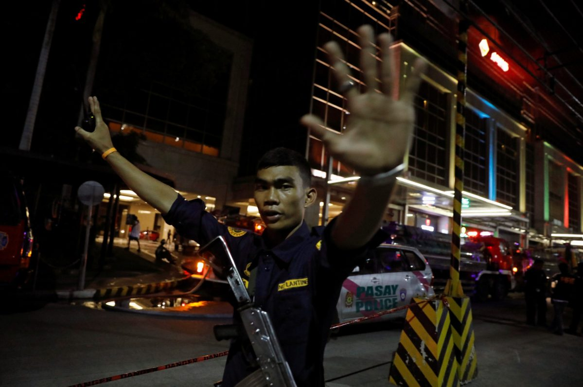 A security guard stops photographers from entering the vicinity of Resorts World Manila after gunshots and explosions were heard in Pasay City, Metro Manila, Philippines June 2, 2017. Photo: Reuters/Erik De Castro