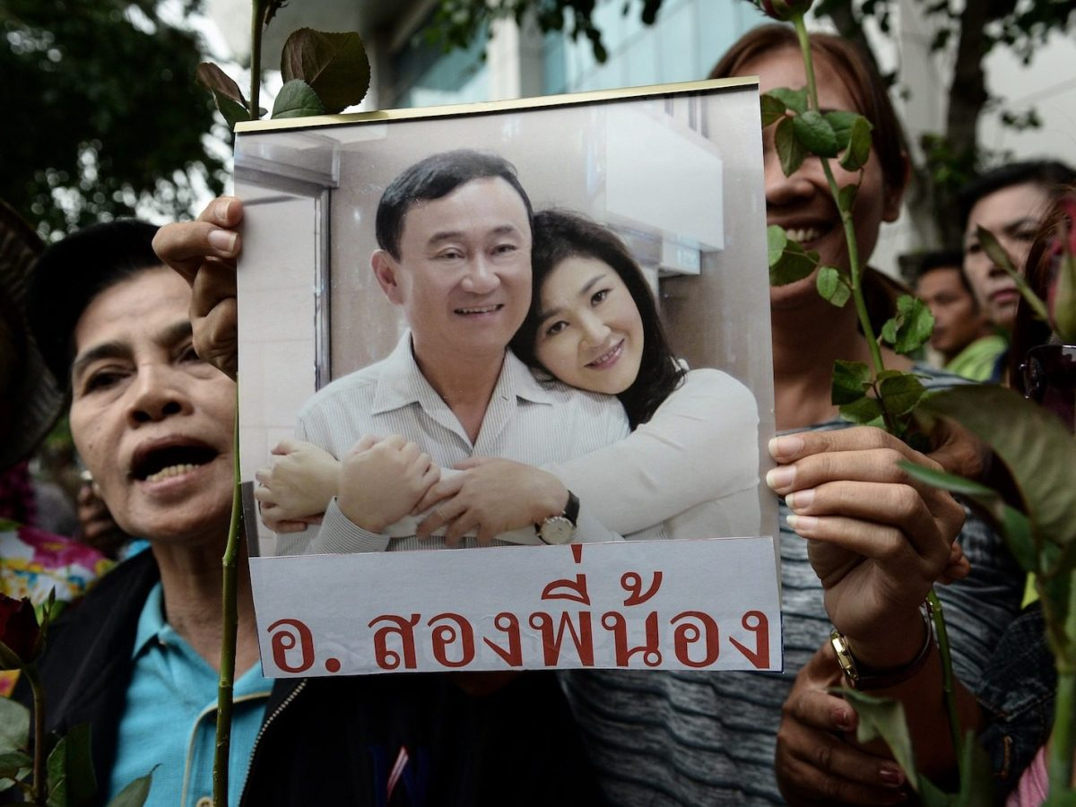 A supporter of former prime ministers Thaksin and Yingluck Shinawatra holds an image them at the Constitutional Court in Bangkok, August 5, 2016. Photo: AFP/ Lillian Suwanrumpha