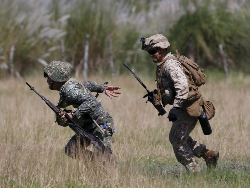 A US Marine from the 3rd Marine Expeditionary Brigade runs with a Philippine soldier during assault exercises in joint drills aimed at enhancing cooperation between the allies at a Philippine Naval base San Antonio, Zambales October 9, 2015.  Photo: Reuters/Erik De Castro