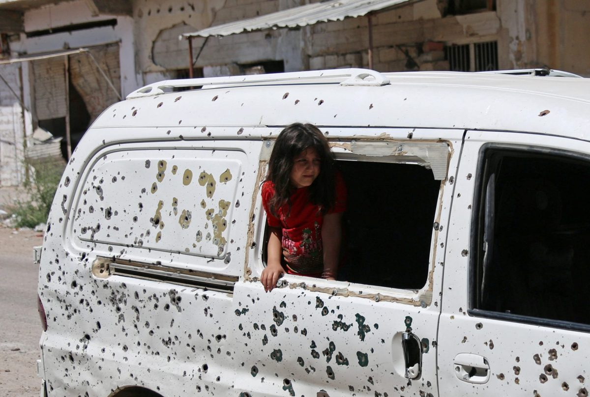A girl looks out from a bullet-riddled bus in a rebel-held part of the southern city of Deraa, in Syria, July 9, 2017.  Photo: Reuters / Alaa Al-Faqir