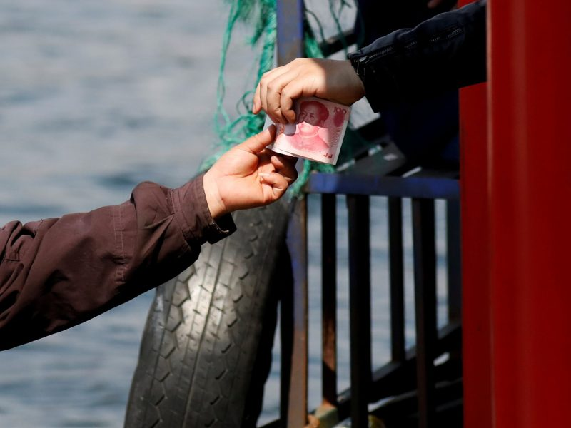 A vendor receives Chinese banknotes after selling North Korean goods to tourists on a boat taking them from the Chinese side of the Yalu river for sightseeing close to the shores of North Korea near Dandong in China's Liaoning Province on April 1, 2017.  REUTERS/Damir Sagolj