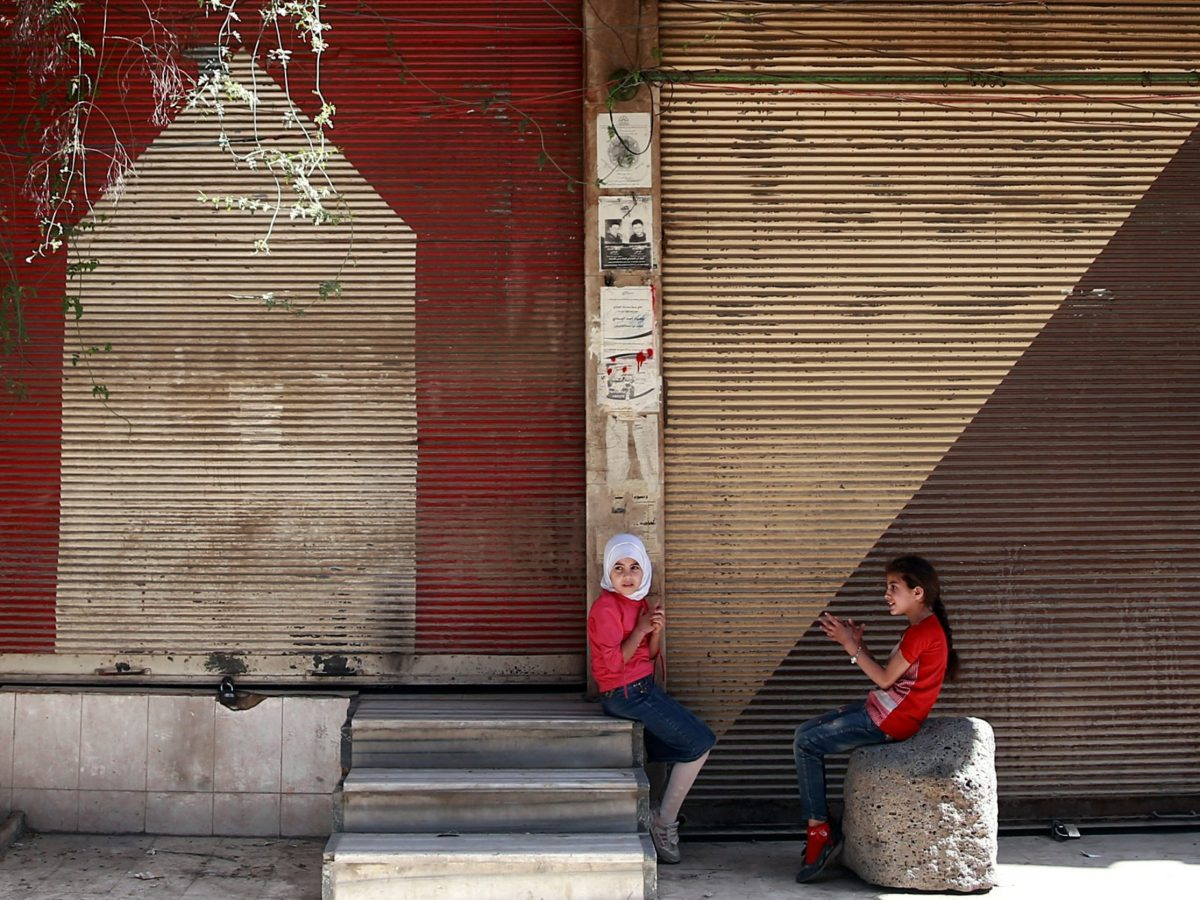 Syrian girls sit in front of shops in the rebel-held Douma neighbourhood of Damascus, Syria, on July 23, 2017. Photo: Reuters / Bassam Khabieh