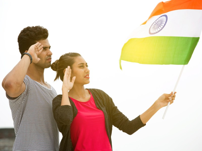 A young couple salute the flag of India. Photo: iStock