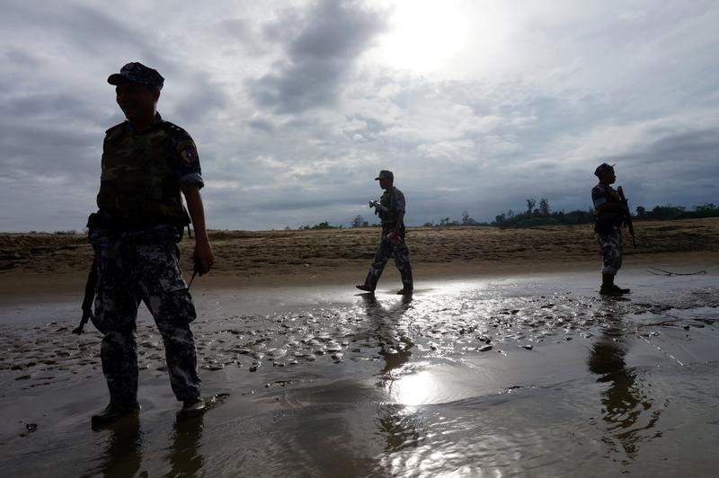 Myanmar security officials stand guard in a pool of mud on July 13, 2017. Photo: Reuters/Simon Lewis
