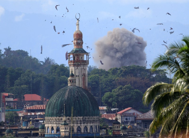 Debris and smoke are seen after an OV-10 Bronco aircraft released a bomb, during an airstrike, as government troops continue their assault against insurgents from the Maute group, who have taken over parts of Marawi city, Philippines.Photo: Reuters/Romeo Ranoco