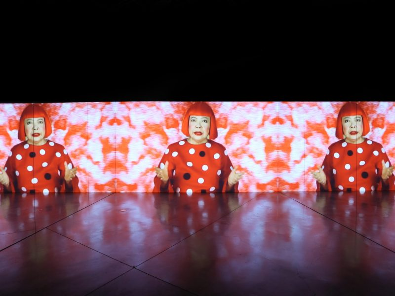 Song of a Manhattan Suicide Addict. This video installation shows the artist singing an original song about her experience dealing with depression. A moving sequence of artworks forms the backdrop. Taking its title from Kusama's acclaimed debut novel, published in 1978, this work provides an insight into her worldview and drive to create art. Collection of the Artist. ©YAYOI KUSAMA. Courtesy of Ota Fine Arts, Tokyo/Singapore, David Zwirner, New York