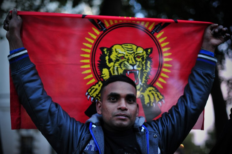 A Britain-based Tamil man holding the flag used by the former seperatist Tamil Tigers movement as he takes part in a protest opposite Downing Street in central London on November 15, 2013 against British Prime Minister David Cameron's visit to Sri Lanka for the Commonwealth Heads of Government Meeting. Cameron arrived on November 14 in Sri Lanka ahead of a Commonwealth summit which is set to be overshadowed by his historic visit to the island's former war zone. Cameron has come under fire from campaigners for not joining the leaders of Canada, India and Mauritius in boycotting the three-day meeting in protest at alleged war crimes committed in the final days of Sri Lanka's decades-long ethnic conflict. AFP PHOTO / CARL COURT / AFP PHOTO / CARL COURT