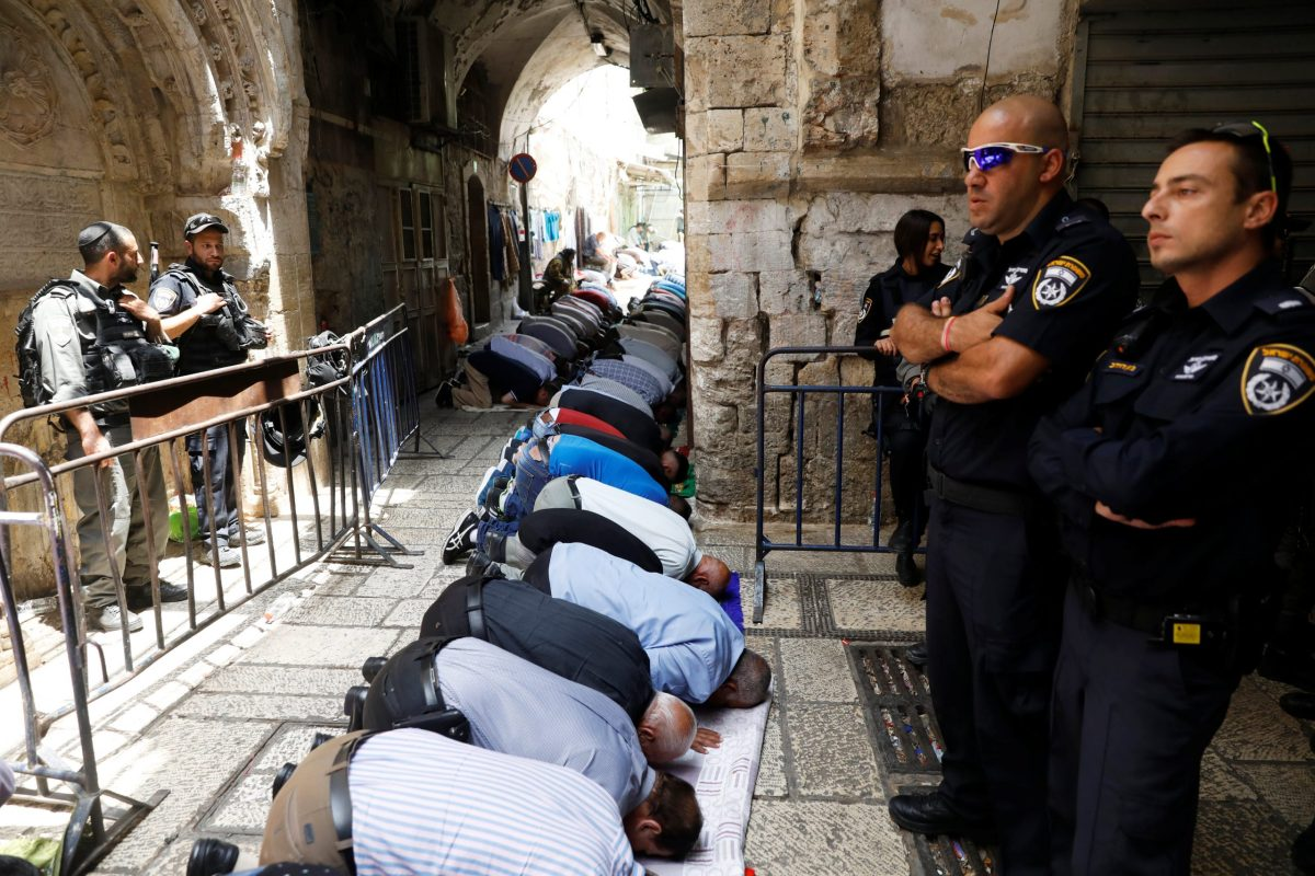 Palestinian men pray as Israeli security forces secure outside the compound known to Muslims as Noble Sanctuary and to Jews as Temple Mount, in Jerusalem's Old City July 26, 2017. Photo: Reuters / Ronen Zvulun