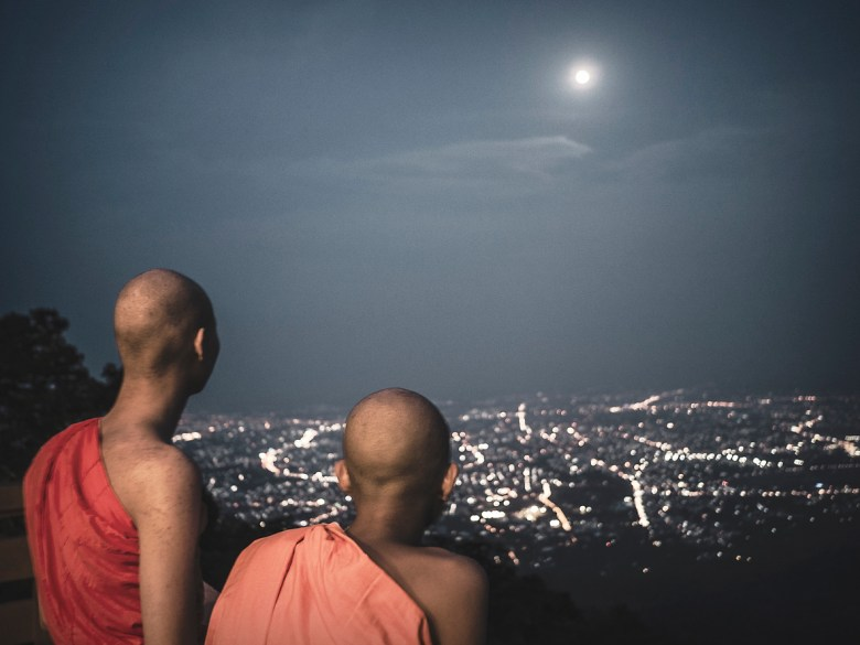 Buddhist monks looking at the full moon at Wat Phra That Doi Suthep Chiang Mai Thailand during the celebration of Visakha Puja the anniversary of Buddha s birth and enlightenment . This is the most important celebration for buddhists and takes place on the full moon day of the sixth lunar month. This temple in the outskirts of the city located on the top of a mountain that overlooks the city is a Theravadada wat was founded in 1383. the Gautama Buddha's shoulder bone is supposed to be housed here as a relic.