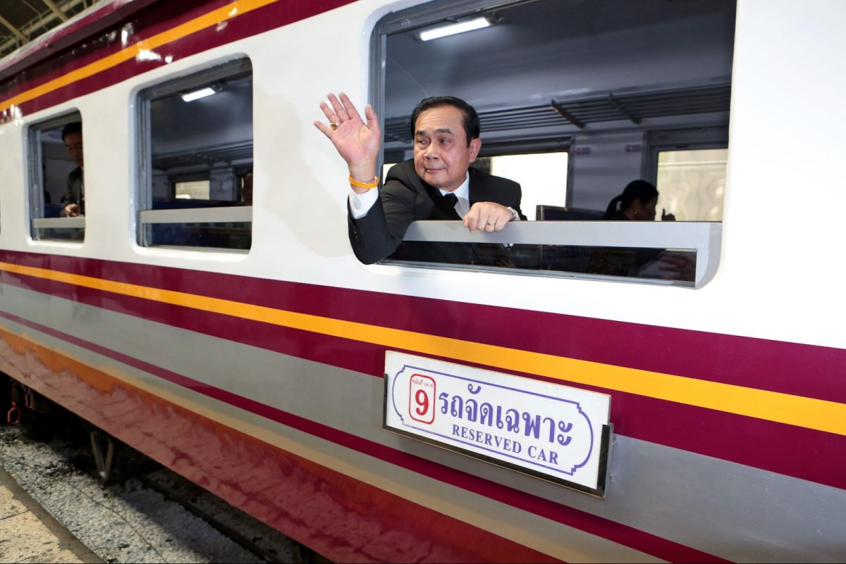 """Thai Prime Minister Prayut Chan-ocha takes a window seat on board a special train. A political foe to Yingluck, he has disavowed the """"rice-for-bullet train"""" agreement with China. Photo: Bangkok Post via AFP/Chanat Katanyu"""