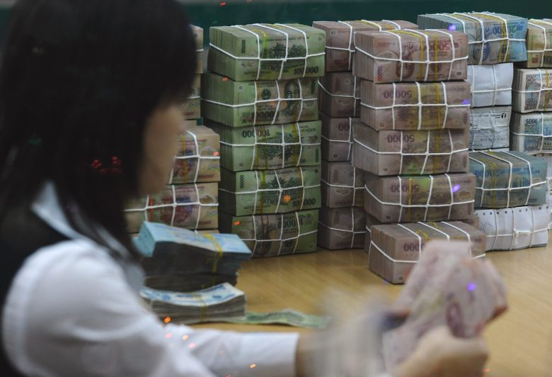 Stacks of the Vietnamese currency, the dong, are counted out by a bank employee in a file photo. Photo: AFP/Hoang Dinh Nam